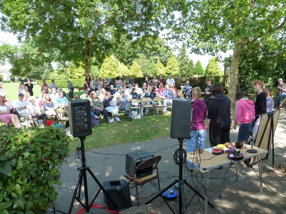 This photograph is taken from just in front of the murals facing the audience. It is a very sunny day.  There is a crowd sitting under the shade of trees in the park. A group of 5 participants is standing at the front performing to the audience. There is equipment for amplifying the sound to the left of the performers.