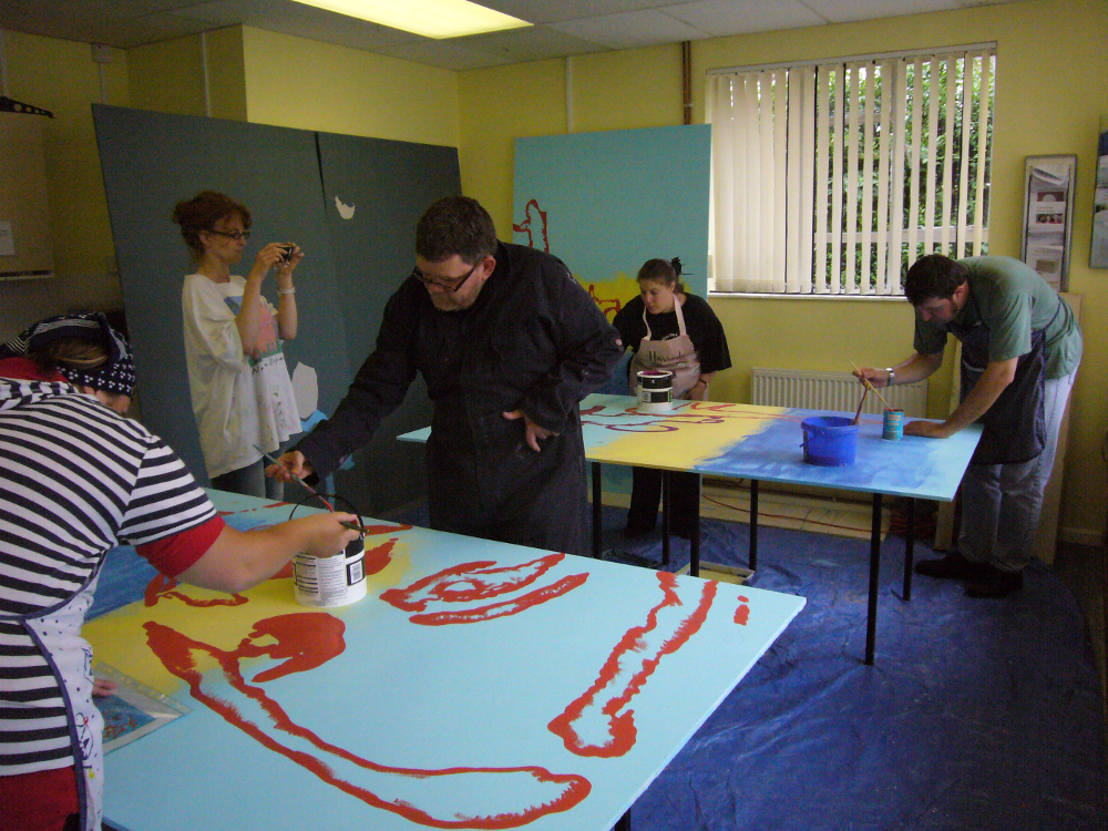 In this picture four people are busy painting on boards laid across tables. The peoples' faces are not clearly visible as they are bent over the boards. There is a man and a woman working on the board at the front, and a man and a woman working at the back. Another woman is standing with a camera. The board at the front of the picture is painted with a pale blue background and a large red silhouette of a face. The board at the back is painted in 3 stripes � dark blue at the bottom, yellow in the middle and pale blue at the top.