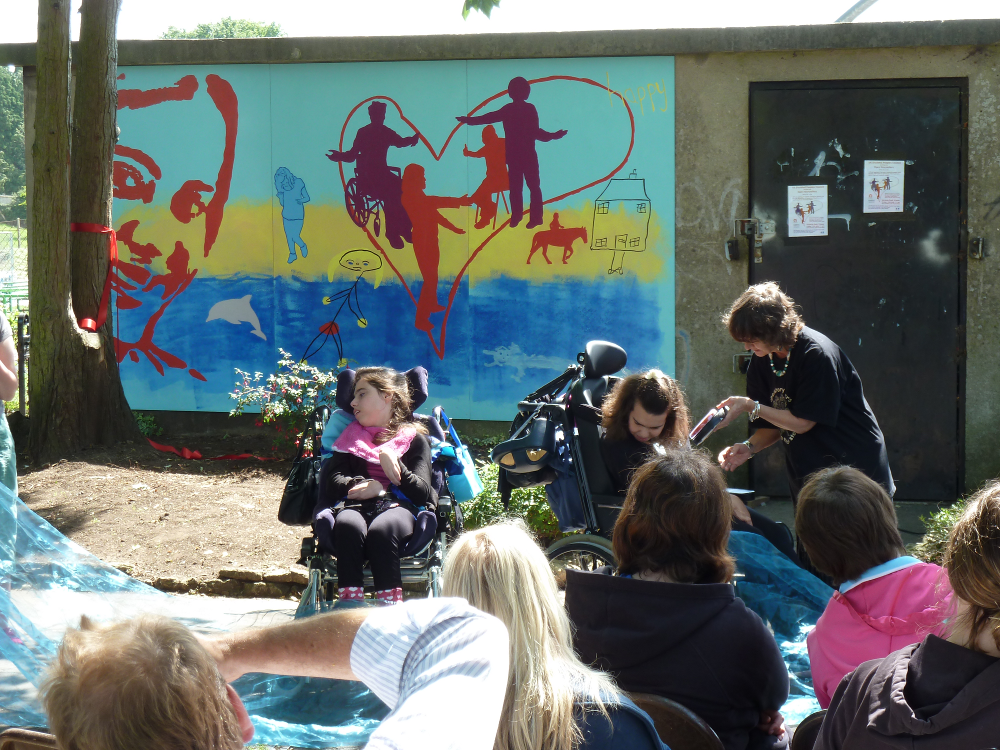 This photo shows two wheelchair users in front of the Happy section of the mural.