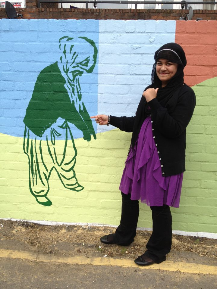 The photo is of a teenage girl who is looking at the camera whilst pointing to a figure that is part of the mural. The figure is herself, painted in green on a background of blue and yellow pointing at the ground.