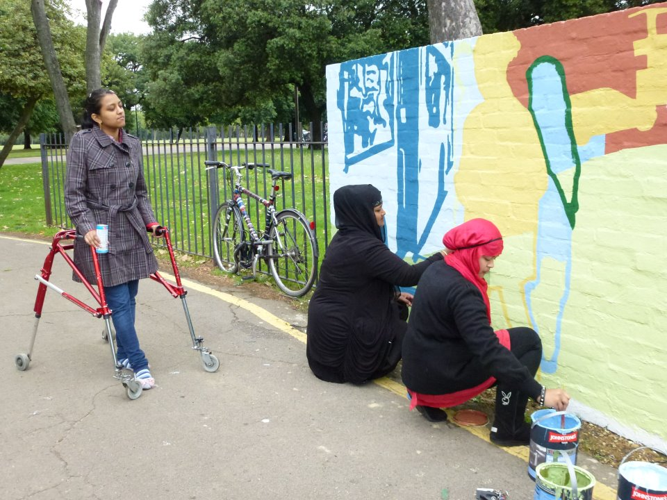 There are two women crouching down painting the mural, they are both wearing headscarves. They are painting a figure in yellow and a figure in light blue. A woman walking with a frame is watching them. She is wearing jeans and a checked jacket and has dark hair tied back in a pony-tail.