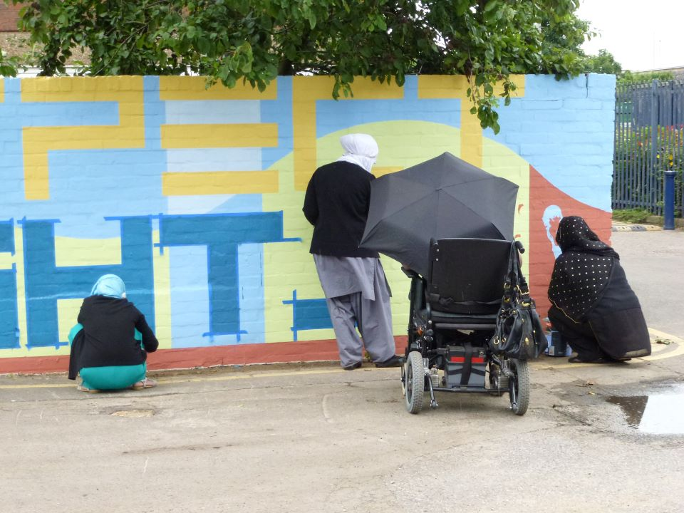 Four women are painting on the wall. They are painting the background and the letter PECT in yellow and HTS in blue from the words RESPECT and RIGHTS. Two women are crouching down, they are wearing headscarves, one woman is a wheelchair user and is holding an umbrella and the other woman is standing up to paint.