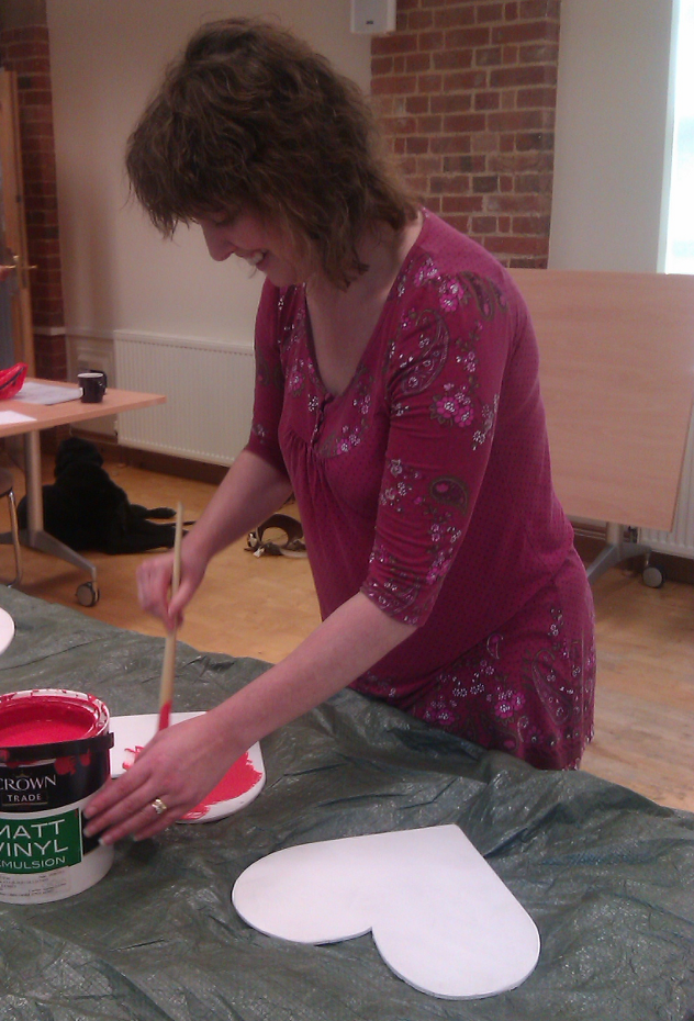 A woman is  smiling as she paints red paint on a white small piece of wood. The shape of the wood is hidden behind the paint pot. The woman has long wavy hair. She is wearing a pink top with flowers on it.