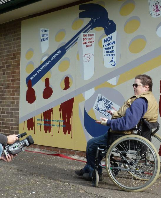 This picture shows a wheelchair user on the right hand side. She has short hair, is wearing glasses, a green sleeveless jacket on top of a blue jumper and jeans. She has her hands palms up in front of her and is talking in front of the section of the mural with the blue hammer and the square pegs being squashed through round holes. The image of the person screaming is in the bin just above her hands.  A film camera can be seen at the bottom right.