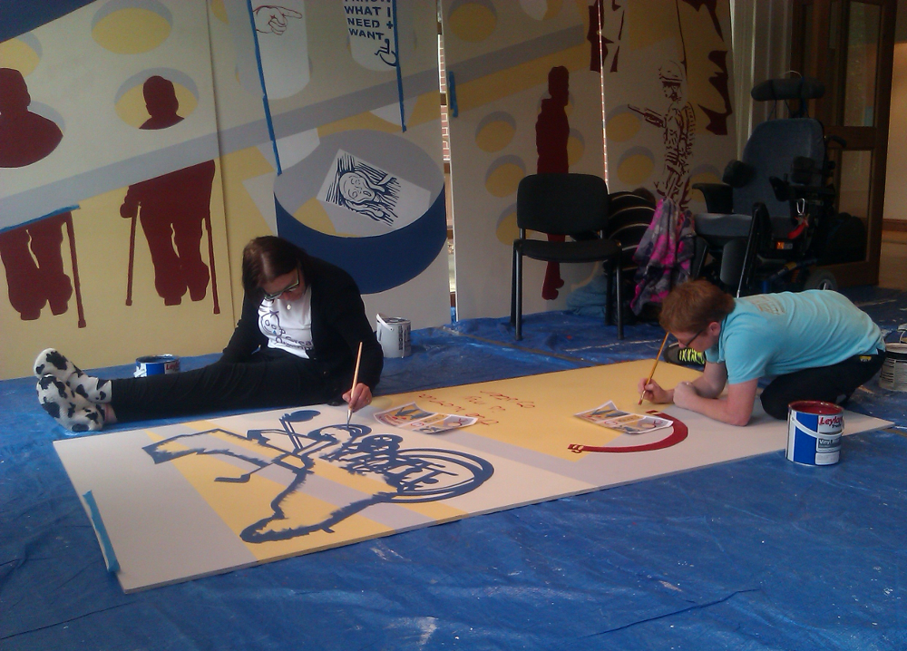 This pictures shows two people painting on a board on the floor. One woman is sitting on the floor with her legs straight in front of her.  She is dressed in black trousers, black cardigan, white t shirt with a drawing on it, and black and white slippers. She is painting the dark blue outline of someone in a wheelchair. The other woman is kneeling and bent over the board as she is painting. She is wearing a light blue t shirt and black trousers. She is painting a dark red semi-circle. Both women are wearing glasses. At the back there are two more boards propped against the wall.  These are the boards for the long wall of the mural in Norwich. There are dark red figures using crutches with their heads sticking out of circular holes, next to them a bit lower down is a dark blue circular bin with a picture of a screaming face inside it. On the right there is a pile of chairs hiding most of the painted boards.